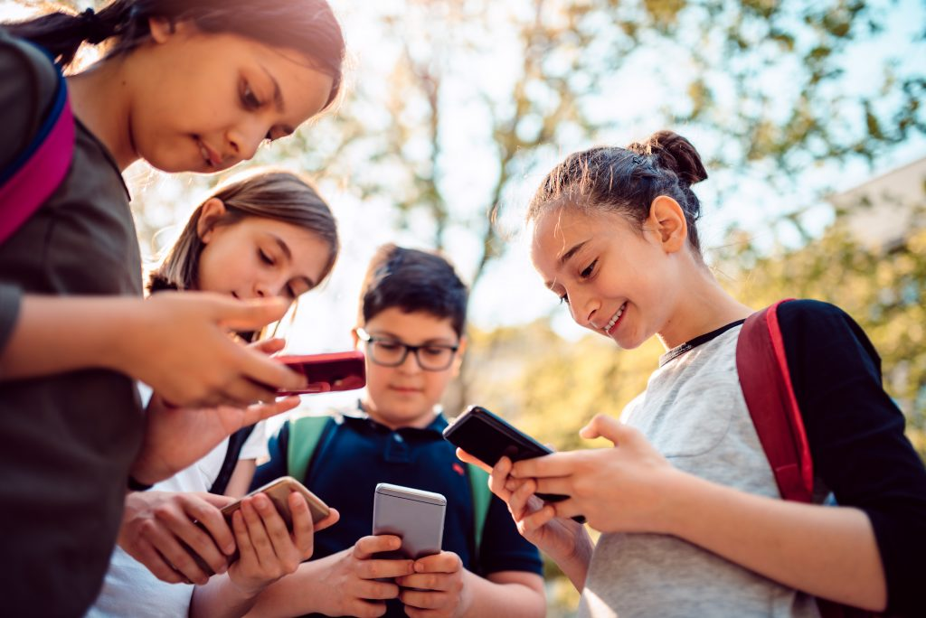 Kids using social media on smart phone after school