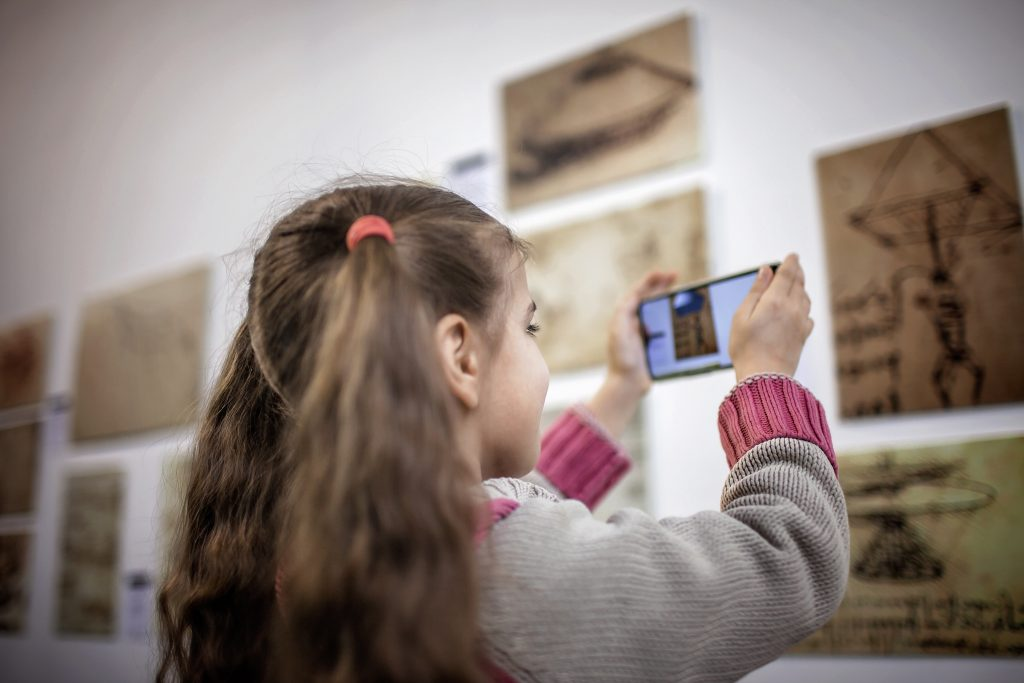 Curious girl exploring a contemporary art exhibition with augmented reality mobile application, future technology in everyday life, indoor lifestyle