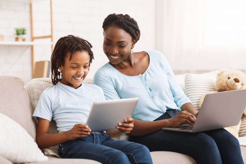 Mother keeping kid safe online while they enjoy screen time together