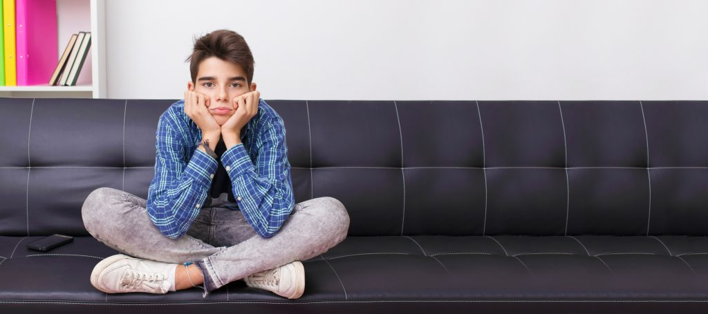 young teenager boy on sofa with bored expression